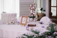 Gasttabelle, mit Blumenstrauß von der Baumwolle und Rahmen mit Zahl Lizenzfreie Stockbilder