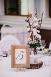 Gasttabelle, mit Blumenstrauß von der Baumwolle und Rahmen mit Zahl Stockbilder