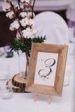Gasttabelle, mit Blumenstrauß von der Baumwolle und Rahmen mit Zahl Lizenzfreie Stockfotografie