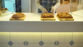 Gastvrij vriendschappelijk meisje met heerlijke roompastei bij bakkerij stock video