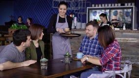 Gastvrije jonge serveerster bij de koffie brengende dranken in gekleurde mokken aan de cliënten Vier vrienden die bij zitten stock videobeelden
