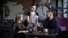 Gastvrije jonge serveerster dichtbij de lijst die betaling van cliënten goedkeuren met behulp van POS-Terminal Mensenzitting bij stock video