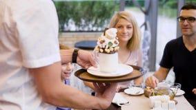 Gastvrije kelner die aan de lijst lopen die smakelijk dessert met slagroom en chocolade voor weinig cliënt brengen gelukkig stock video
