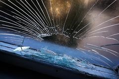 Gat in het glazen venster door een kogel die tijdens oorlog het schieten wordt geschoten Barsten die rond het gat uitspreiden Gro royalty-vrije stock foto's