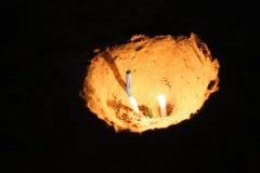 Gat in het zand met het branden van kaarsen Stock Foto's