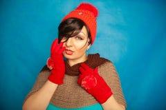 Gat tricoté rouge de port d'hiver de mode de jolie fille de brune et beaux gants chauds sur le fond solide de studio bleu image stock