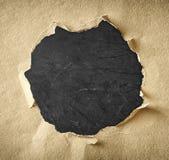 Gat van gescheurd document over geweven zwarte achtergrond wordt gemaakt die Royalty-vrije Stock Afbeelding