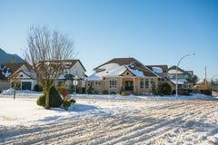 Gata av bostads- hus i snö på solig dag för vinter Royaltyfri Fotografi