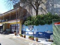 Gata av lilla staden med gatamålarfärgkonst på väggen, Europa arkivbilder