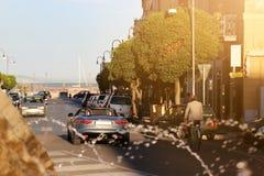 Gata för sjösidastad med den luxuty konvertibla bilen som går till marina Liten semesterortstad på havet solig ljus dag Lyxig sem Arkivbilder