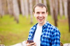 Gata för stad för stiligt leende för manmobiltelefonappell utomhus-, för skjortabruk för ung attraktiv grabb blå smartphone royaltyfria foton