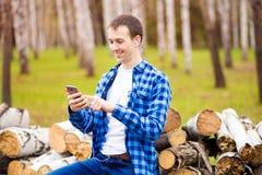 Gata f?r stad f?r stiligt leende f?r manmobiltelefonappell utomhus-, f?r skjortabruk f?r ung attraktiv grabb bl? smartphone royaltyfria bilder