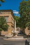Gata med byggnader och springbrunn, solig eftermiddag i Aix-en-provence Arkivbild