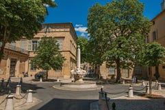 Gata med byggnader och springbrunn, solig eftermiddag i Aix-en-provence Fotografering för Bildbyråer