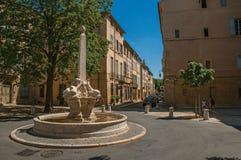 Gata med byggnader och springbrunn, solig eftermiddag i Aix-en-provence Arkivfoto