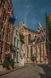 Gata med flaggor, tegelstenhus och kyrkan på Bruges Arkivbild