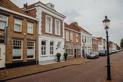 Gata med tegelstenhus på molnig dag i byn av Geertruidenberg Royaltyfria Foton