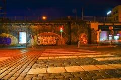 Gata på natten utanför gammalt grungy område av staden med gatakonst Royaltyfri Fotografi