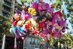 Gata som försäljer färgrika tecknad filmfolieballoonss som visar cartoo Fotografering för Bildbyråer