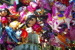 Gata som försäljer färgrika tecknad filmfolieballoonss som visar cartoo Royaltyfria Foton