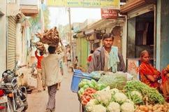 Gataaffärsman som kommer med morötter, zucchini, blomkål till bygrönsakmarknaden av den indiska staden royaltyfri bild