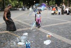 Gataaktör som skapar bubblor i storformat för ungar på Central Park i New York Fotografering för Bildbyråer