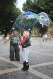 Gataaktör som skapar bubblor i storformat för ungar på Central Park i New York Royaltyfri Bild