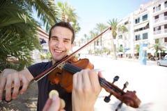 Gataaktör som spelar fiolen som betalas pengar Royaltyfri Bild