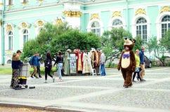 Gataaktörer i dräkter av tecknad filmtecken underhåller turister i St Petersburg arkivfoton