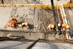 Gataarbetare som häller cement med en pump in i en huvudvägconstru Arkivfoton