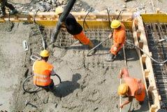 Gataarbetare som häller cement med en pump in i en huvudvägconstru Royaltyfri Bild