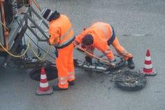 Gataarbeten på avkloppkanalen med varnar undertecknar in tyska ord för kanalarbeten royaltyfri foto