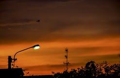 Gatabelysning och bakgrundssolnedg?ngljus reflekterat med molnet arkivbilder