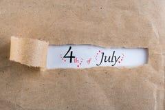 Gataclownen hälsar folk Juli 4th Bild av den juli 4 kalendern på brun sönderriven kuvertbakgrund field treen Royaltyfria Bilder