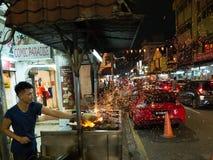 Gatagatuförsäljare som lagar mat Claypot ris med att flyga för gnistor Arkivfoton