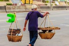 Gatagatuförsäljaren går med bär bambukorgar av grillat eg. Arkivfoton