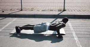 Gatagenomkörare Den idrotts- afrikansk amerikanmannen som gör push-UPS, och snurrandet övar på utomhus En svart man spelar arkivfilmer