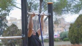 Gatagenomkörareutbildning Arg passformman som gör handtag-UPS med motståndsmusikbandet på utomhus- idrottshall i parkera lager videofilmer