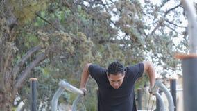 Gatagenomkörareutbildning Den latinamerikanska mannen som gör den parallella stången, doppar med motståndsmusikbandet på utomhus- arkivfilmer