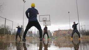 Gatagenomkörareutbildning Sportgrupp av ungt mång- etniskt folk som öva tai-chistansmaskiner på den utomhus- basketen arkivfilmer