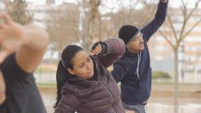 Gatagenomkörareutbildning Sportgruppen av tre unga etniska personer som gör sidoräckviddövning i hösten, parkerar i stock video