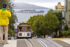 Gatakabelbil i San Francisco som går sluttande till möte av det Alcatraz fängelset upptill av Hyde Street Royaltyfri Foto