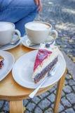 Gatakafé i Weimar, Tyskland Två koppar kaffe latte och ett stycke av kakan Arkivbild
