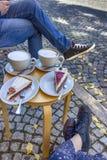 Gatakafé i Weimar, Tyskland Två koppar kaffe latte och stycken av kakan arkivfoto