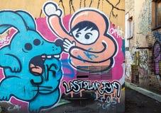 Gatakonst, gammal vägg med grungy tecknad filmgrafitti Arkivbild