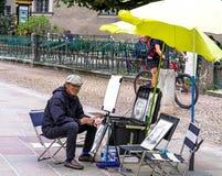 Gatakonstnär-illusionist som utför svävningtrick i den gamla mitten av Salzburg, Österrike Arkivfoton
