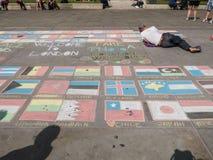 Gatakonstnären arbetar på flaggor av världsskärmen på betong på Arkivfoton