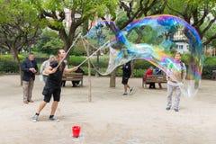 Gatakonstnären gör stora såpbubblor Arkivfoton