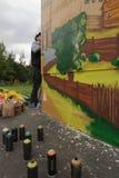 Gatakonstnären målar grafitti på väggen Arkivfoton