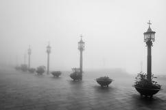 Gatalampor med katoliken korsar i en dimmig dag Arkivfoto